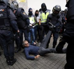 Spanish police clear the entrance of a polling station in Barcelona, on October 1, 2017, on the day of a referendum on independence for Catalonia banned by Madrid.  More than 5.3 million Catalans are called today to vote in a referendum on independence, surrounded by uncertainty over the intention of Spanish institutions to prevent this plebiscite banned by justice.  / AFP PHOTO / PAU BARRENA